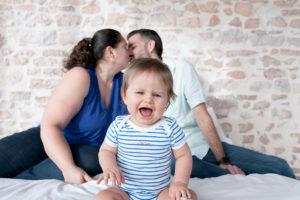 Parents s'embrassant devant bébé.