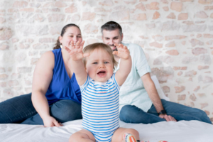Bébé heureux sous le regard de ses parents.